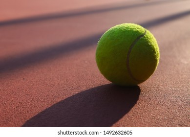 Tennis ball on the tennis court.Tennis balls are covered in a fibrous felt which modifies their aerodynamic properties
