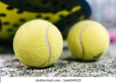 tennis ball on the green artificial grass court after a paddle tennis match. ball next to the net of a paddle tennis court