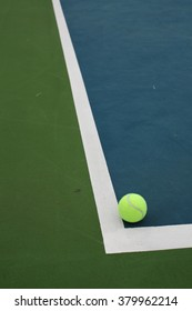 Tennis Ball on Green and Blue Court with White Line in Corner