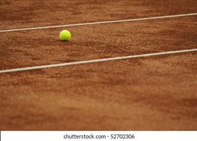 Tennis ball on the orange tenniscourt