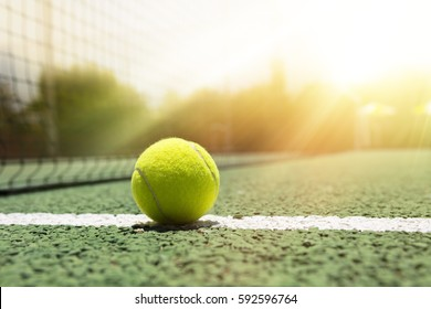 Tennis ball on a outdoor green hard court