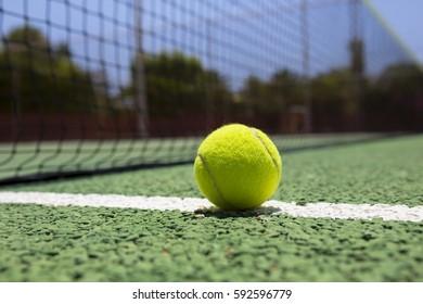 Tennis ball on a outdoor green hard court