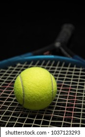 Tennis ball on a racket on black organic glass