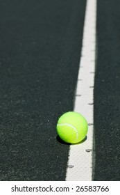 tennis ball on serve line of court