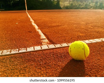 Tennis ball on the service line. Close up of tennis clay court. Mobile stock photo taken with smartphone