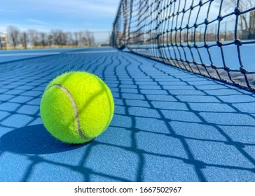 Tennis ball on a soft blue court next to the net. outside tennis court
