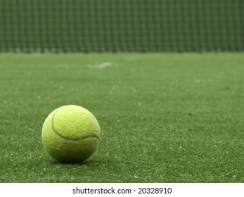 Tennis ball on synthetic grass of tennis court.
