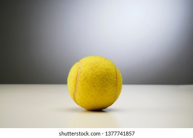 Tennis ball on white and grey background.