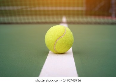 Tennis ball on the white line in the green court