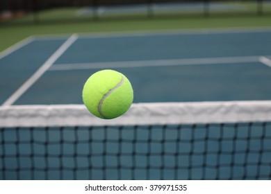 Tennis Ball Over Net on Blue Green Court