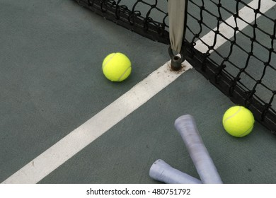 tennis ball, racket grip and net on hard court