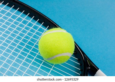 Tennis ball and racket on blue background