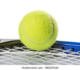 Tennis ball and racket over white background