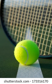 Tennis Ball with Racket Strings in the background