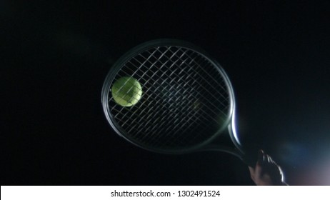 Tennis ball and racquet isolated on black background playing tennis at night closeup of ball being hit