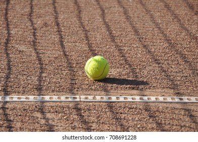 Tennis ball and shadow of the grid.