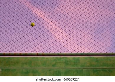 Tennis ball stuck on a steel net.