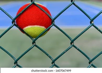 tennis ball stuck on the wire fence of a outdoor court horizontal composition