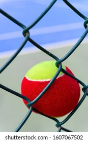 tennis ball stuck on the wire fence of a outdoor court vertical composition