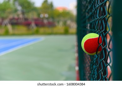 tennis ball stuck on the wire fence of a outdoor court