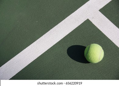 Tennis ball and white lines on green tennis court