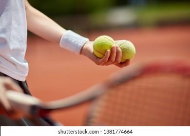 Tennis balls in player's hand on tennis court