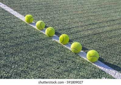 Tennis balls laid out in a row on a white line on a tennis court