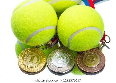 Tennis balls and medals on the mirror on white background