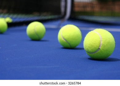 Tennis balls on a blue court right to left