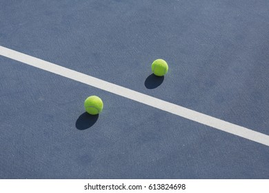 tennis balls on blue hard court divided with white line