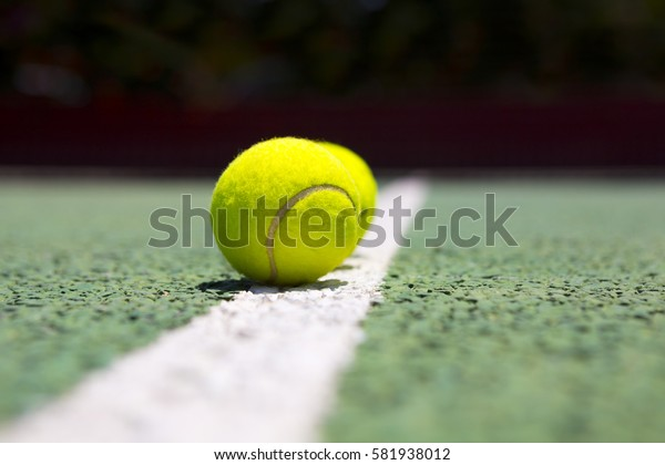 Tennis balls on a green tennis hard court