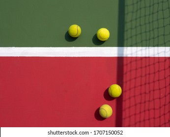 Tennis balls on hard court with casted shadow of net