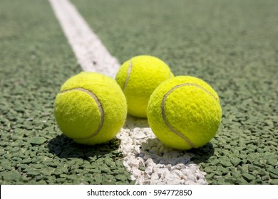 Tennis balls on a outdoor green hard court
