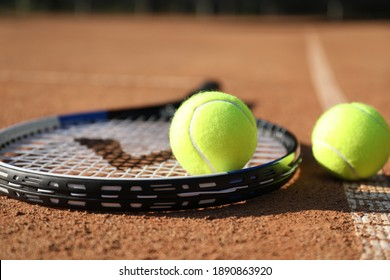 Tennis balls and racket on clay court, closeup