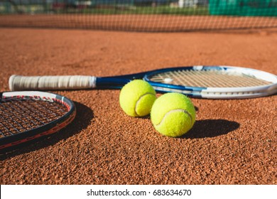 Tennis balls and racket on the clay court