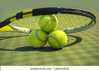 Tennis balls and racket on the grass court. Close-up.