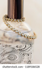 Tennis bracelet in gold and diamonds placed around a perfume bottle