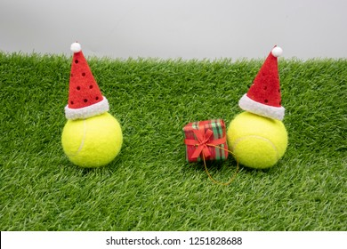 Tennis Christmas with tennis ball and Santa hat on green grass