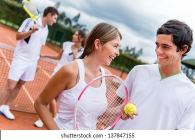 Tennis couple at the court playing doubles and looking happy