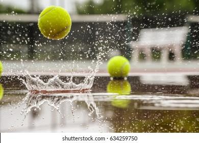 Tennis court. Hard court in raining weather. Yellow tennis ball bouncing
