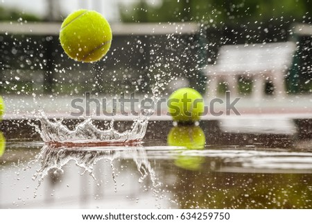 Tennis court. Hard court in raining weather. Yellow tennis ball bouncing