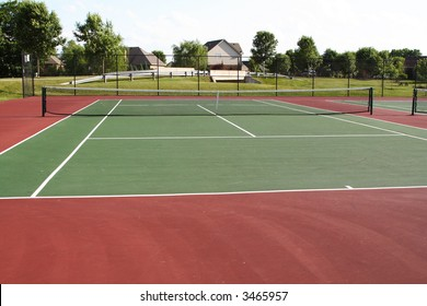 Tennis court playing surface and net