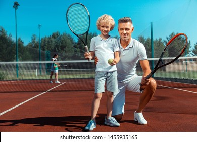 Tennis with daddy. Cute curly son feeling happy while playing tennis with daddy at the weekend