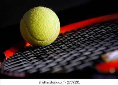 Tennis equipment - ball and racket on black. Soft light, shallow depth of field.