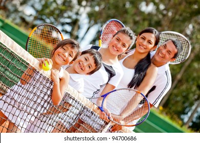 Tennis family standing in a row by the net