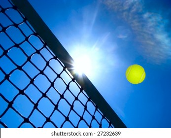Tennis game concept with ball flying over the net under the blue sky.