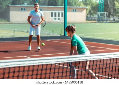 Tennis with girl. Father wearing white t-shirt and shorts playing tennis with his active lovely girl