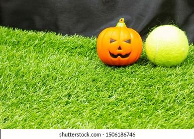 Tennis Halloween with pumpkin are on green grass.