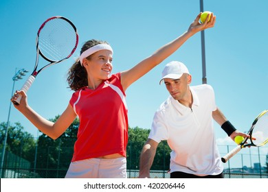 Tennis instructor polishing serving power posture with student