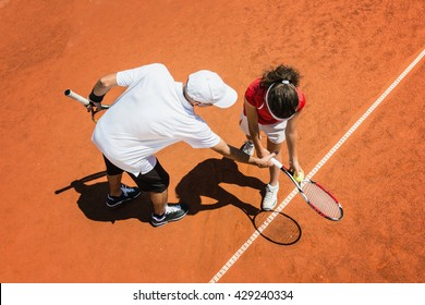 Tennis instructor working with young student